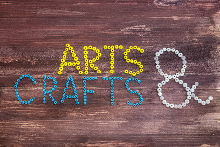 craft background: \Arts & Crafts\ written in beads on a wooden background