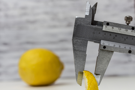 Measuring a Lemon Slice with the use of a Vernier Caliper Stock Photo