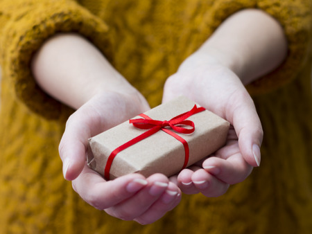 Woman's hand giving a gift box