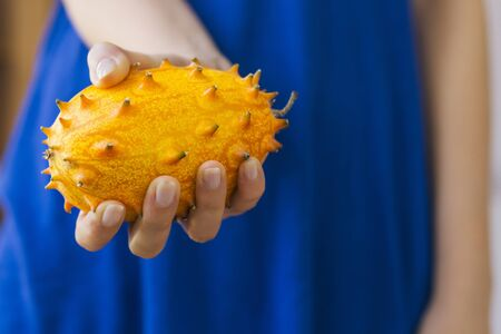 hedged: Woman holding an African Horned Melon