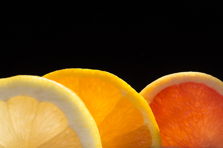 Backlit citrus fruits slices on a dark background