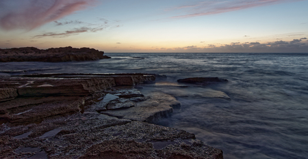 Landscape of rocky shoreline with tranquil waves and sun going down sea, Israel.
