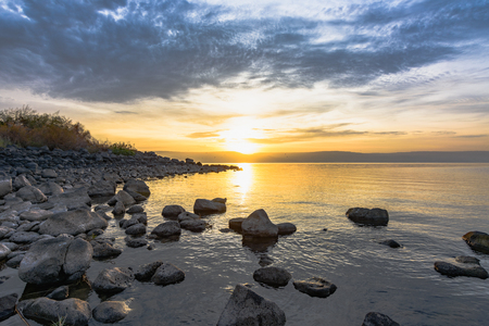 Amazing sunset on seaside with rocks