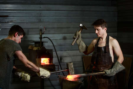 two blacksmiths in the apron and chain mail forge the product in the smithy
