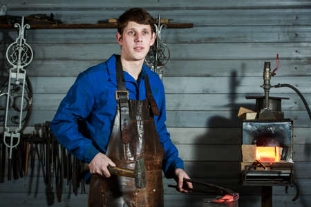 portrait of a young blacksmith in a leather uniform works in a smithy