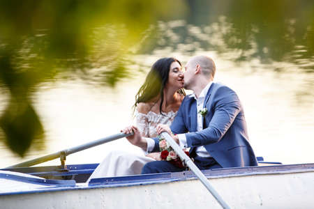 Wedding Couple Bride and Groom in the Park Pond in the Pleasure Boat.  posing in boat at lake in forest Stockfoto