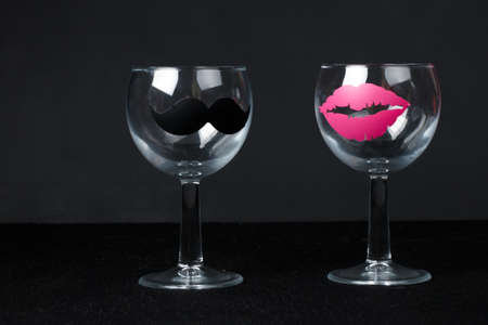 glasses for wine with a sticker in the form of mans mustache and female lips  close up on the dark black background.funny glasses Stockfoto