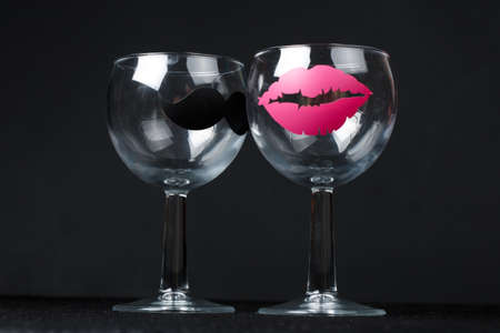 glasses for wine with a sticker in the form of man's mustache and female lips  close up on the dark black background.funny glasses