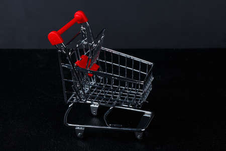 toy mini muniature shopping cart, grocery trolley on black dark background Stock Photo