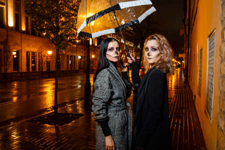 Outdoor night portrait of two young beautiful  girl holding transparent umbrella with garland, posing in street of european city. rain. Banque d'images - 98442952