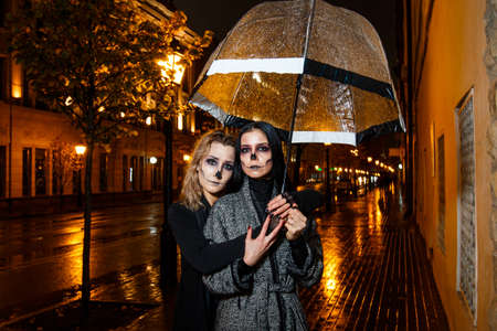 Outdoor night portrait of two young beautiful  girl holding transparent umbrella with garland, posing in street of european city. rain. Banque d'images - 98442951