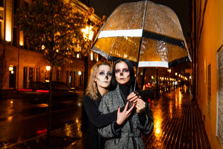 Outdoor night portrait of two young beautiful  girl holding transparent umbrella with garland, posing in street of european city. rain. Banque d'images - 98442789