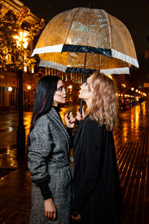 Outdoor night portrait of two young beautiful  girl holding transparent umbrella with garland, posing in street of european city. rain. Banque d'images - 98442734