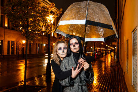 Outdoor night portrait of two young beautiful  girl holding transparent umbrella with garland, posing in street of european city. rain. Banque d'images - 98442736