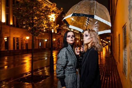 Outdoor night portrait of two young beautiful  girl holding transparent umbrella with garland, posing in street of european city. rain. Banque d'images - 98442738