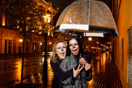 Outdoor night portrait of two young beautiful  girl holding transparent umbrella with garland, posing in street of european city. rain. Banque d'images - 98442741