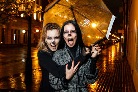 Outdoor night portrait of two young beautiful  girl holding transparent umbrella with garland, posing in street of european city. rain. Banque d'images - 98442743