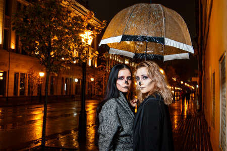 Outdoor night portrait of two young beautiful  girl holding transparent umbrella with garland, posing in street of european city. rain. Banque d'images - 98442746