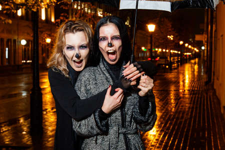 Outdoor night portrait of two young beautiful  girl holding transparent umbrella with garland, posing in street of european city. rain. Banque d'images - 98440396