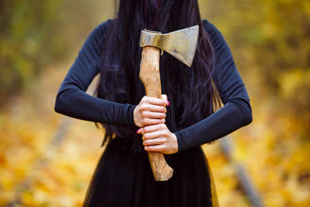 a girl in a witch costume in a long black dress with long black hair covering her face holds an ax in her hands. Day, autumn, a tunnel of yellow autumn leaves.thematic photossesion Stock Photo