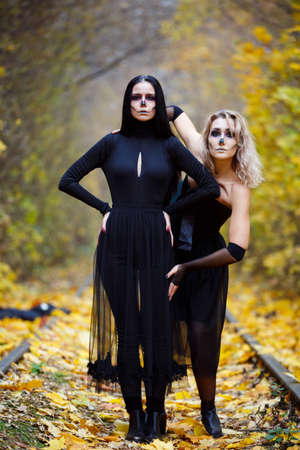Two young beautiful sexy witches in black gowns standing in the middle of burnt meadow with predatory face expression. Halloween concept. Outdoors shot.