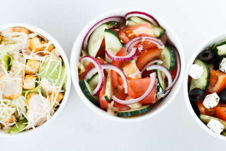 3 different salads isolated on white background, top view, menu. greeck salad, cesar, salad with onion cucumber and tomates Stock fotó