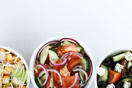 3 different salads isolated on white background, top view, menu. greeck salad, cesar, salad with onion cucumber and tomates Banco de Imagens