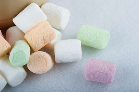 Spilled colored marshmallows from a mug on white  background close up