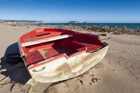 lonliness: View of this red wreck boat in this lonliness beach.