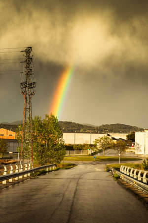 View of rainbow after big spring storm in small industrial village. photo