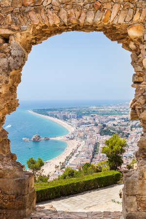 View of Blanes through a stone door of the St. John Castle of Blanes in summertime.