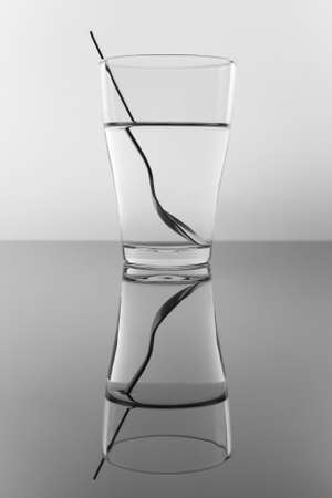 Example of the water refraction with a glass and spoon. Stock Photo
