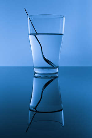 Glass of water with spoon in blue background with reflection.