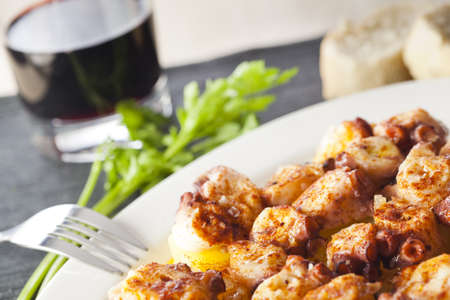 Typical spanish meal with octopus, potatoes, coarse salt, paprika and olive oil. Original dish from Galicia, Spain. Stock Photo