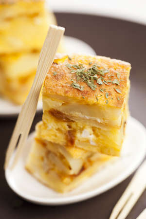 toothpick: Portion of a spanish potato omelet called tapa or pincho, typical spanish pub food. Focus on parsley. Stock Photo