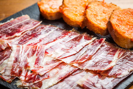 Spanish jabugo ham with bread and tomato. Stock Photo