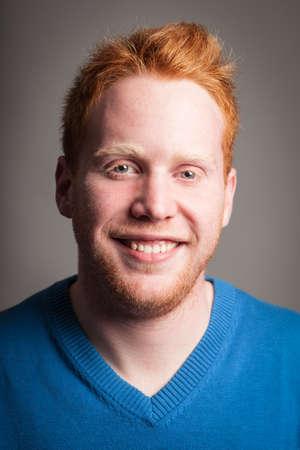 Redhead boy smiling looking at camera.