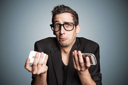 Young businessman with broken smartphone.