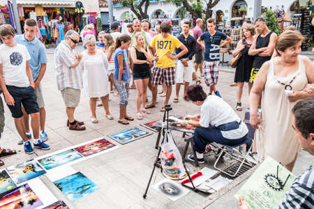 TOSSA DE MAR, SPAIN - 21 JULY  Tourists look a street artist painter in the street in Tossa de Mar, small touristic village of Costa Brava,   Tossa de Mar July 21, 2013  Editorial