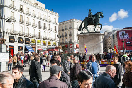 MADRID, SPAIN - 06 DECEMBER  People walk in La Puerta del Sol square, with republican stall in the background, anti royalist political group  Madrid december 06, 2011