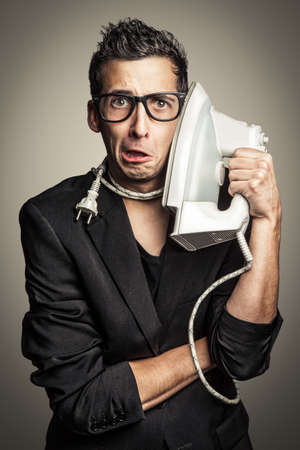 humor: Young businessman is using a flat iron like a phone. Stock Photo