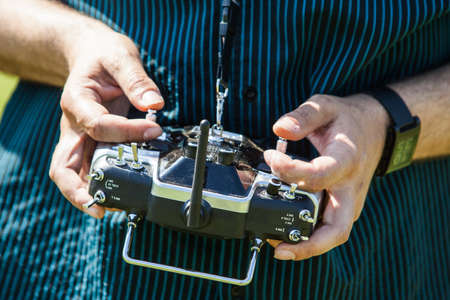 helicopter pad: Hands in remote controller for drive a Drone. Stock Photo
