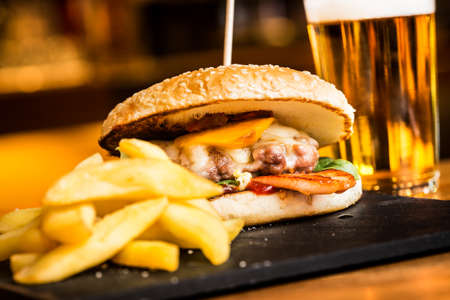 Big cheeseburger with fries and cold beer. Stock Photo