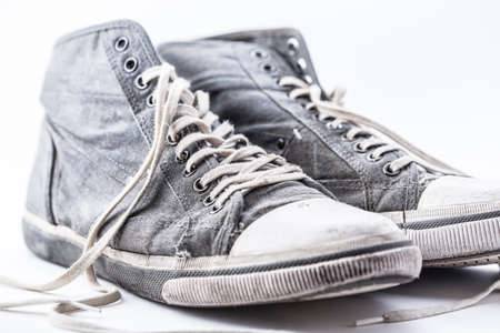 Pair of old and damaged sport shoes. Stock Photo