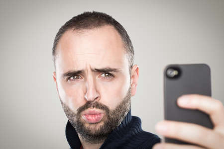 Young man taking a selfie with his phone. photo