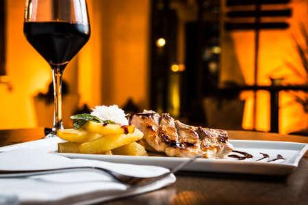 gourmet dinner: Gran filete de cerdo a la parrilla con un vaso de vino tinto. Foto de archivo