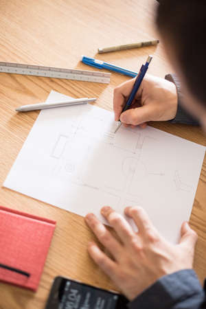 architect drawing: Architect working at his desk drawing a sketch. Stock Photo