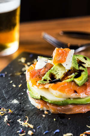 Different smoked salmon salad with avocado and sauce. photo