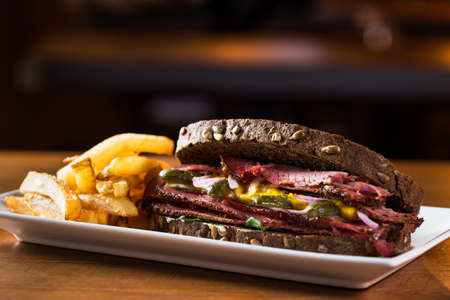 Delicious pastrami sandwich with french fries ready to eat. Stock Photo
