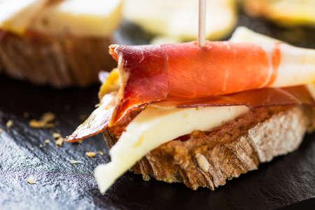 Spanish tapas: slice of bread, cheese and spanish ham. Stock Photo